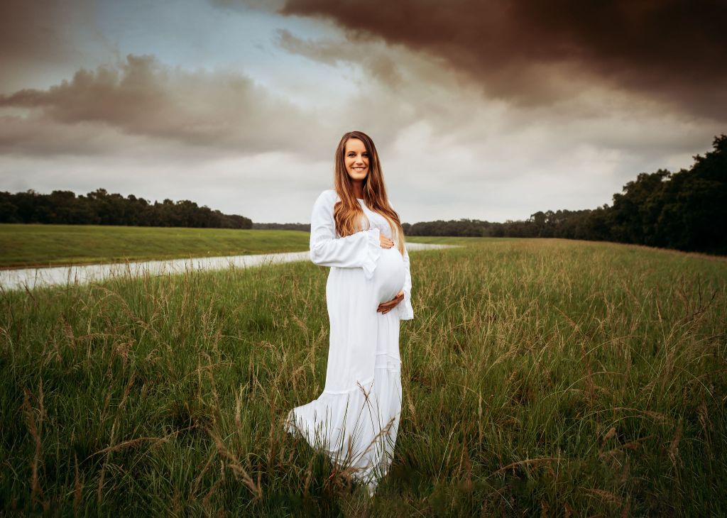 pregnant mother standing in a tampa florida field maternity session